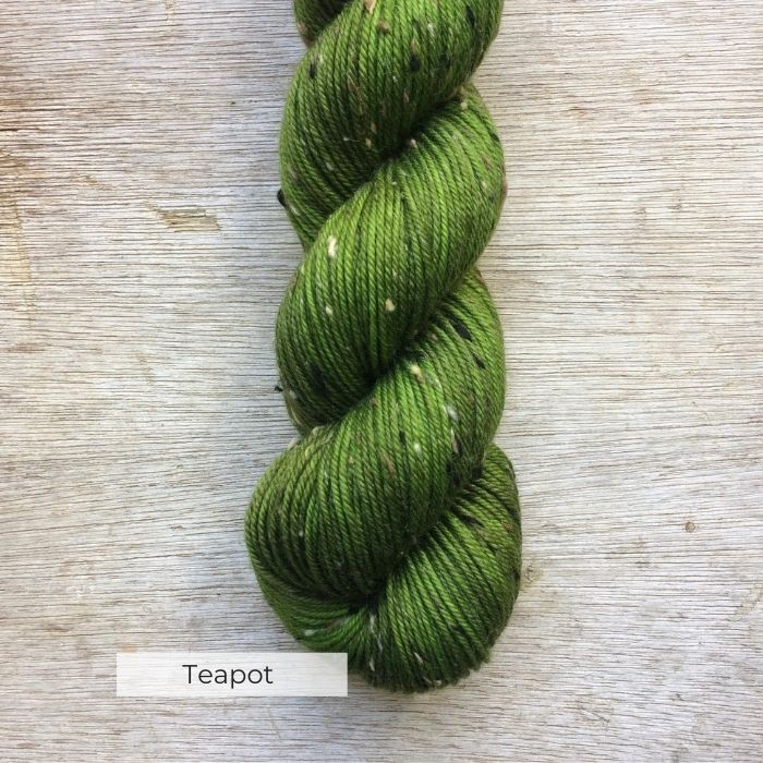 A single skein of tweedy merino in shades of green