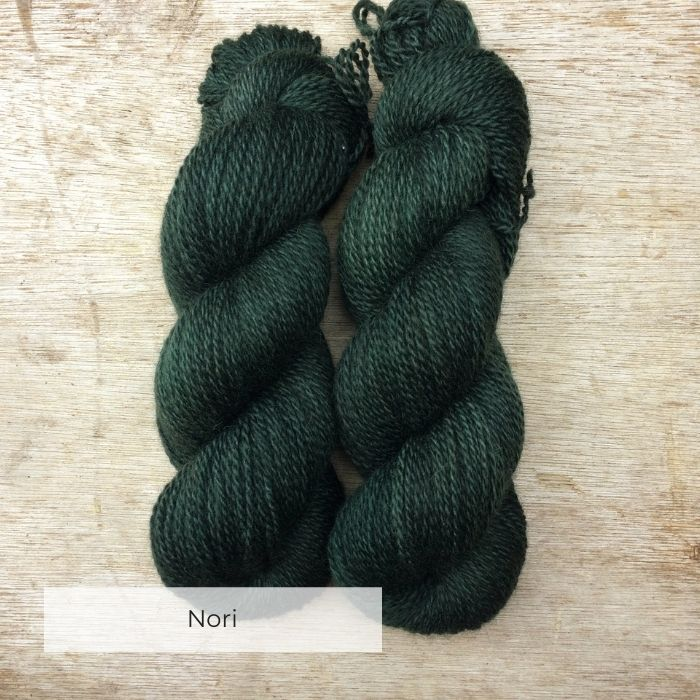 Two skeins of DK rustic yarn in a deep bottle green