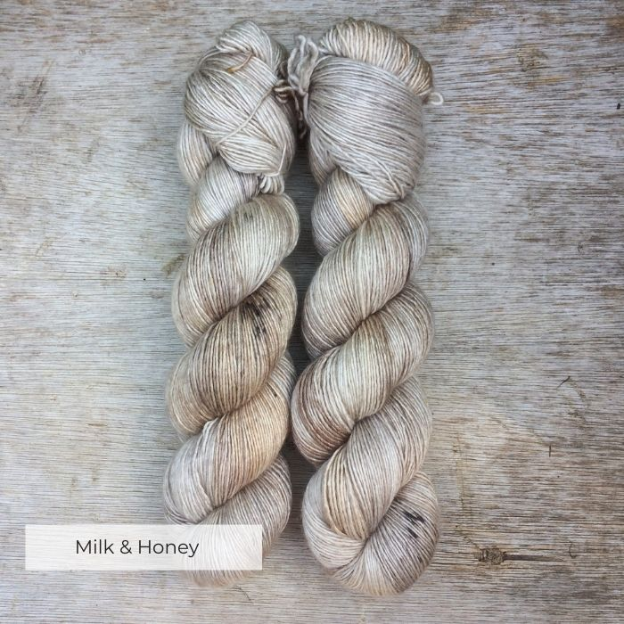 Two skeins of soft yarn in cream, gold and light brown