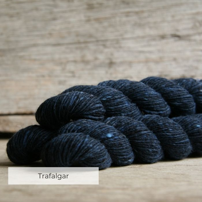Three skeins of of tweedy deep blue yarn with naps of royal blue and grey