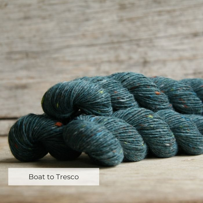Three skeins of petrol blue yarn with coloured neps of orange, lime and grey