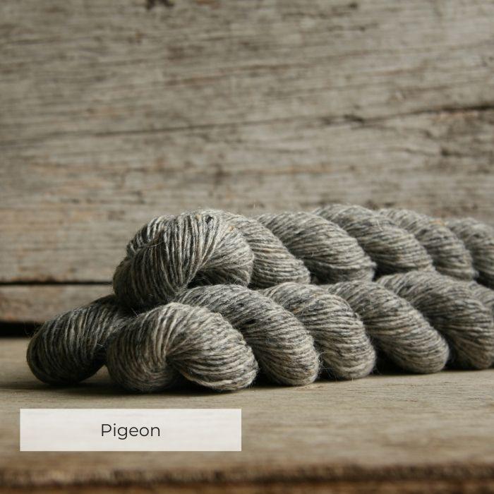 Three skeins of tweedy light grey yarn with naps of white, grey and cream