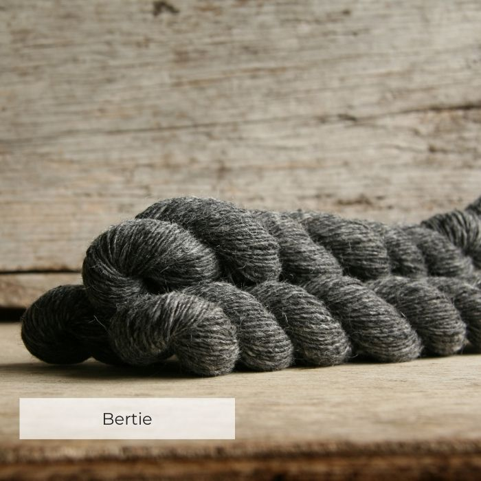 Three skeins of tweedy grey yarn with naps in shades of grey
