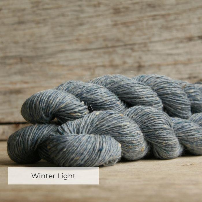 Three skeins of light blue yarn with tweedy naps of cream, grey and blue