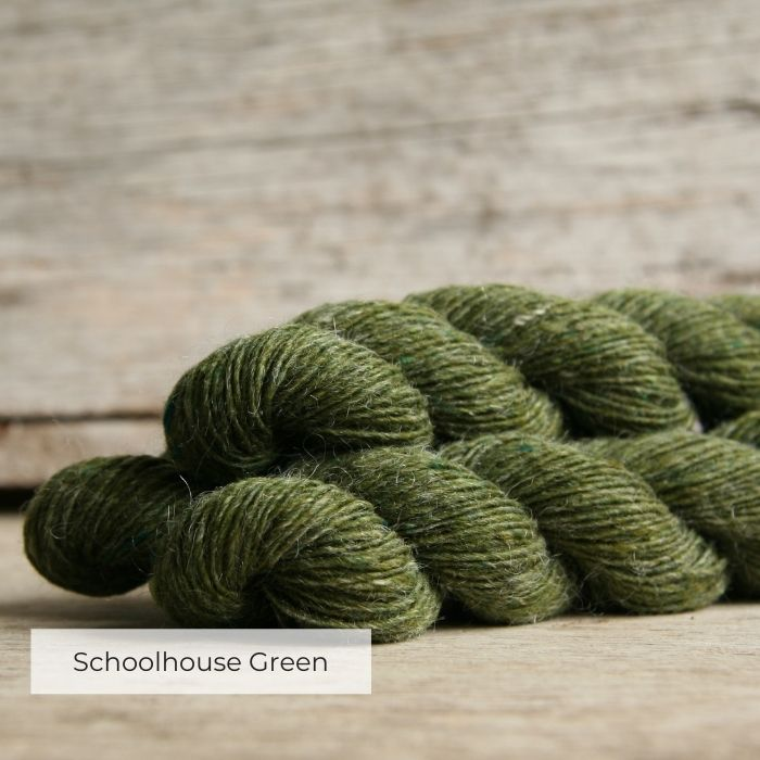 Three skeins of tweedy yarn with naps of grey and bottle green