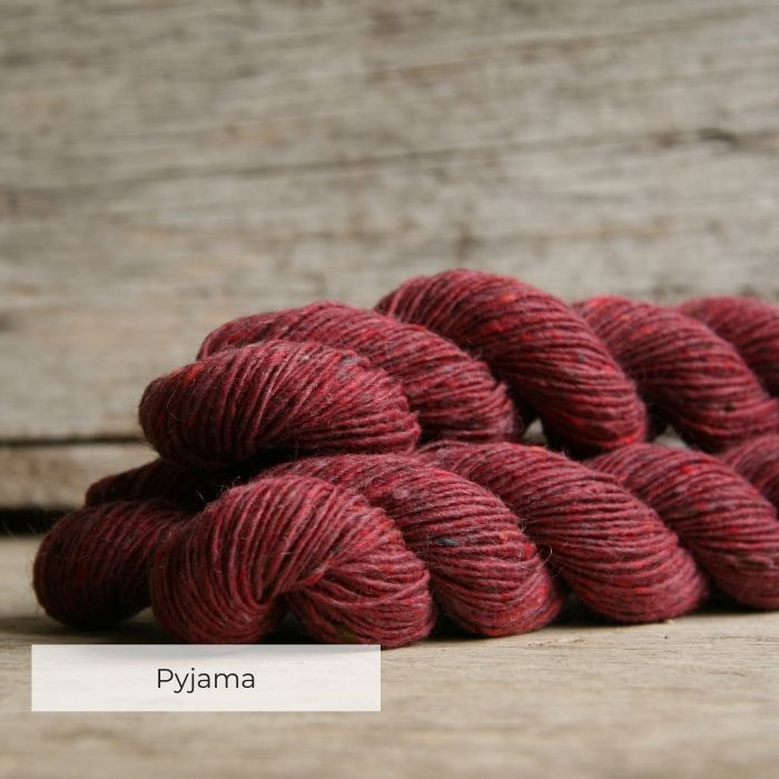 Three skeins of tweedy yarn in a deep rose pink with naps of blue, red and grey