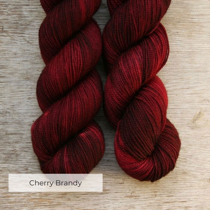 Two plump skeins of wool in shades of deep red