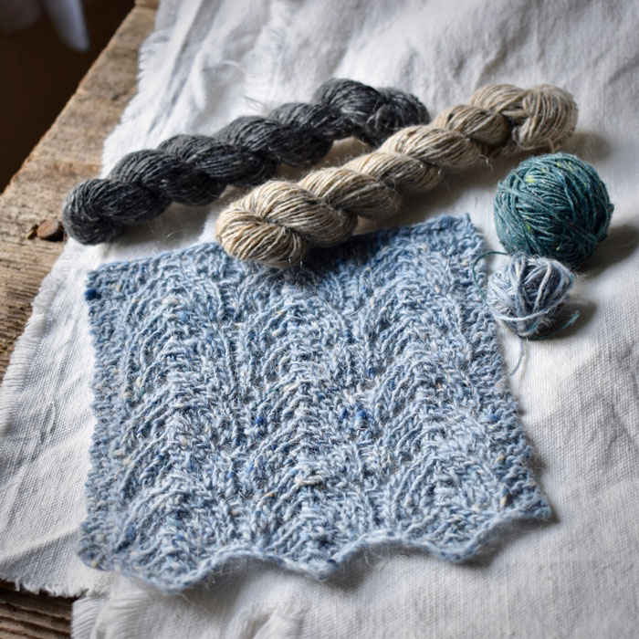 A pale blue knitted lace work sample with tiny balls of tweedy wool