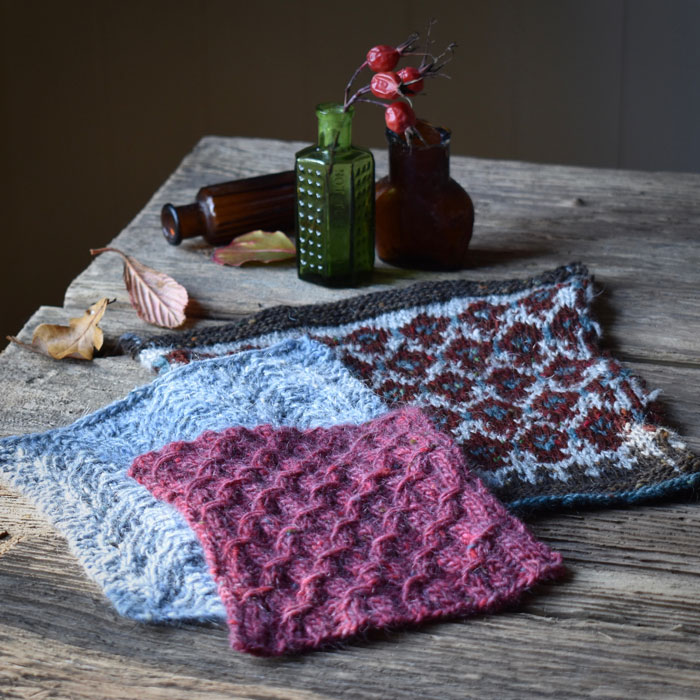 A wooden table top with three knitted samples on it. One colour work, one lace and the third a textured stitch