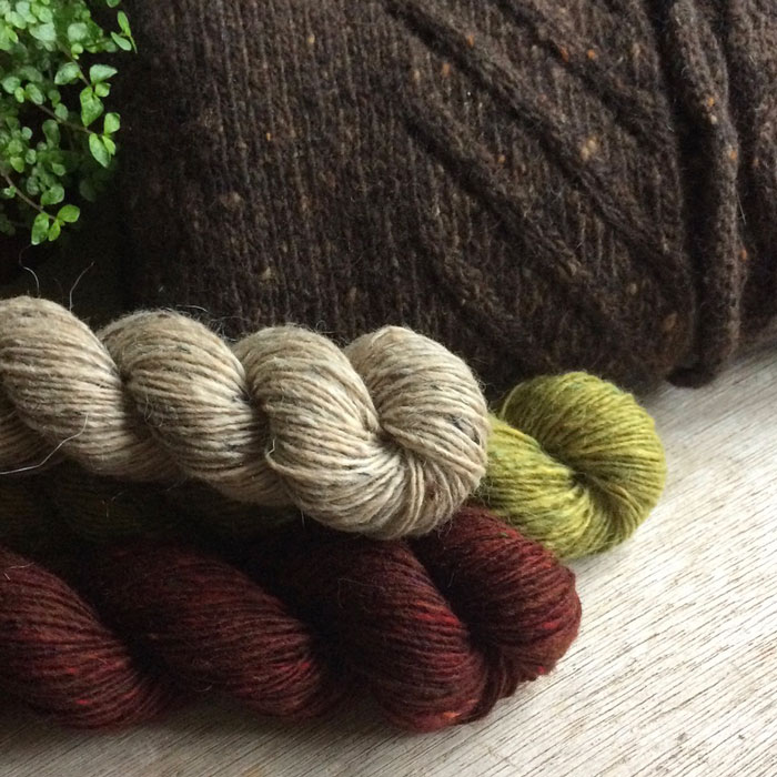 Three skeins of different coloured tweedy yarn stacked up in front of a knitted sample