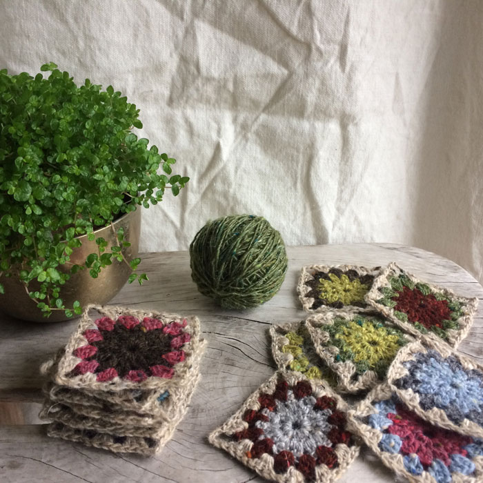A wooden stool top covered with scattered , multi coloured crochet squares