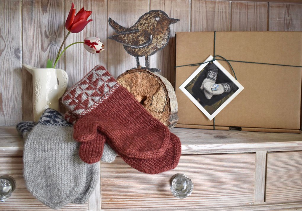 Two pairs of mittens with pattered cuffs on the shelf of a dresser
