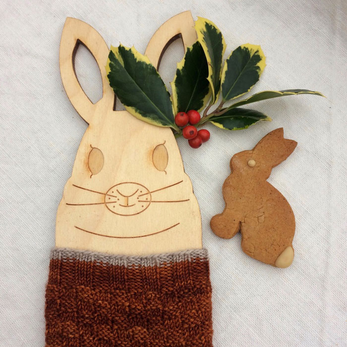 A wooden bunny sock blocker in a ginger sock with a gingerbread rabbit and a sprig of holly