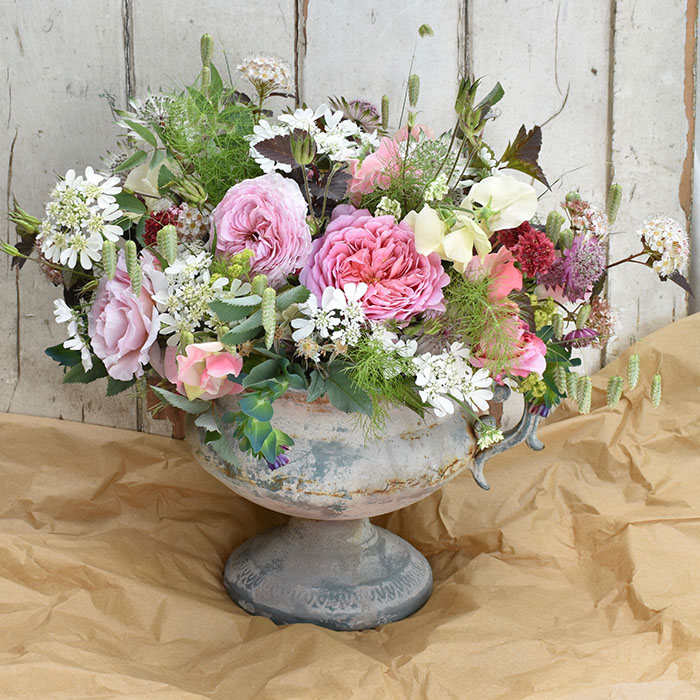 A stone coloured urn filled with lilac roses, sweetpeas and Orlya