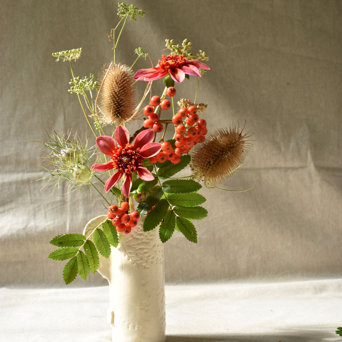 A white jug of autumn dahlias, teasels and seed heads