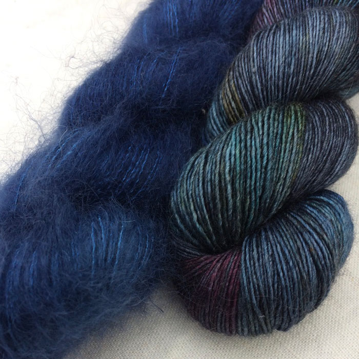 A close up of a rich blue mohair skein and another skein in blues, plums and teals