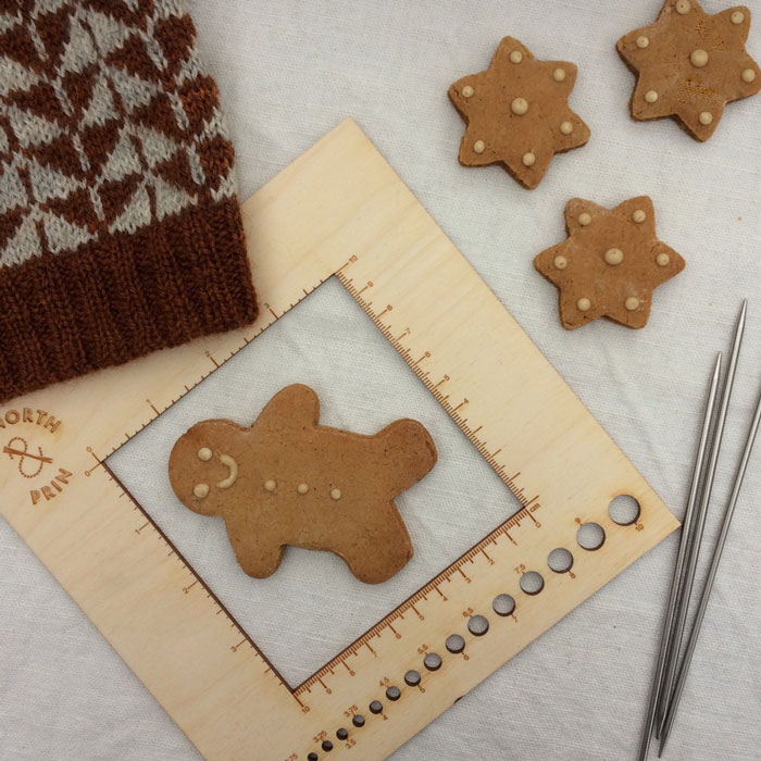A wooden tension gauge on a linen background surrounded by knitting and gingerbread biscuits