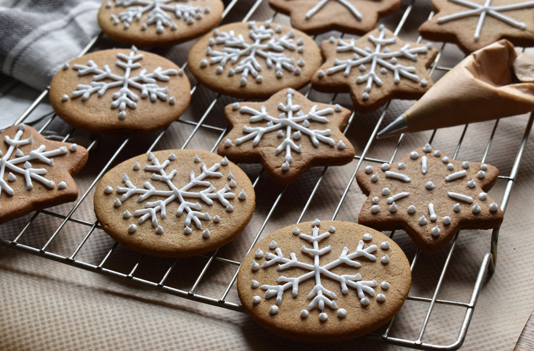 decorating gingerbread shapes with a paper piping bag