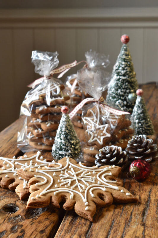 Christmas gingerbread in clear gift bags on a wood surface with Christmas decorations