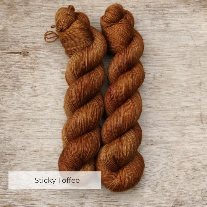 Two skeins of semi solid sock yarn that have been dyed in shades of toffee