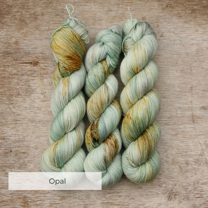 Three skeins of sock yarn dyed in shades of mint, pearl grey and blue with speckles of dark green, rust and brown