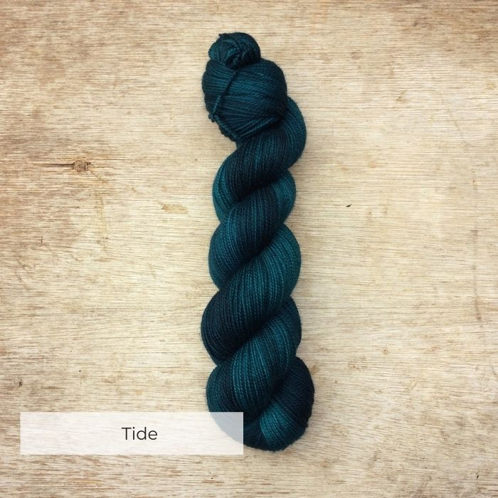 A semi solid skein of green blue yarn