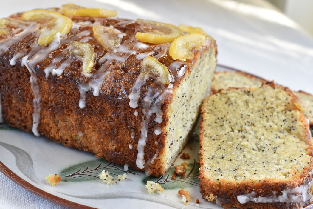 A lemon poppy seed cake on a plate with a slice taken off