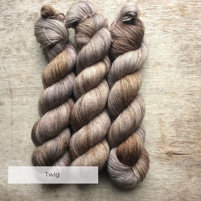 Three skeins of soft and slightly fluffy yarn in shades of brown speckled with red and yellow