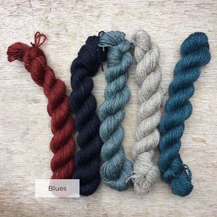 Five little mini skeins in blues and natural with one red
