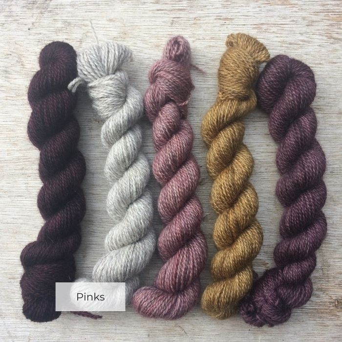 Five curly mini skeins in shades of plum, pink and gold with a natural yarn