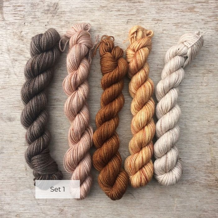 Four mini skeins of yarn in shades of peach and brown