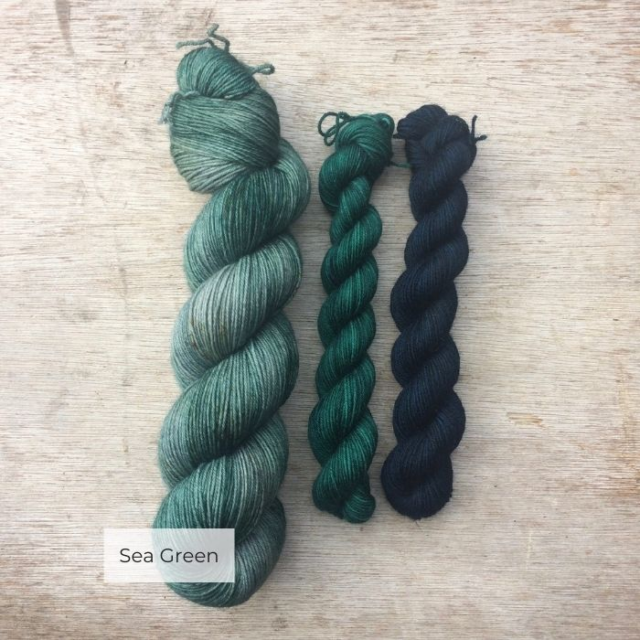 A full skein of speckled blue green yarn with two smaller skeins of yarn in teal and navy