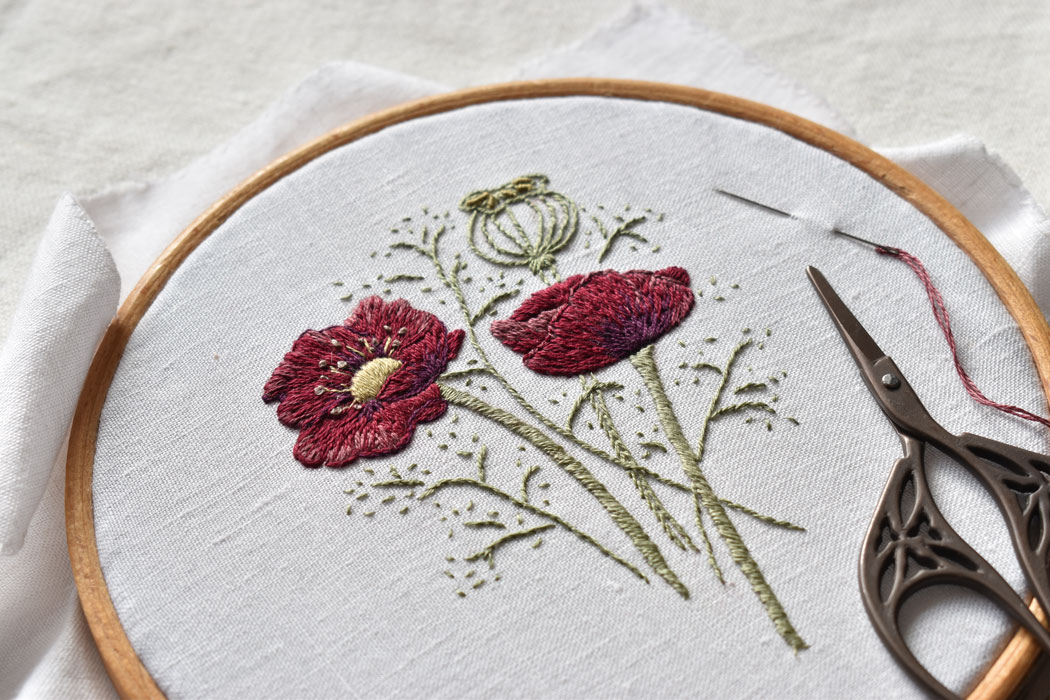 A flower embroidery on white linen in a wooden embroidery hoop
