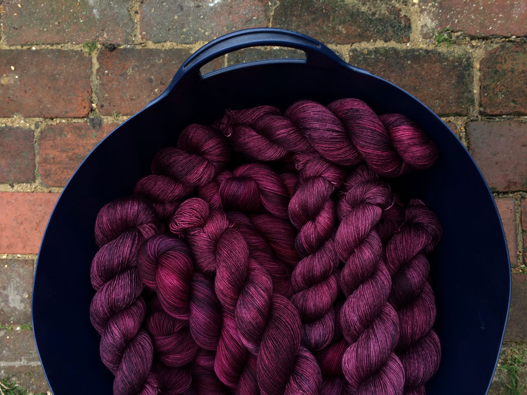 Blue bucket of rich plum coloured yarn twisted up and ready for labelling