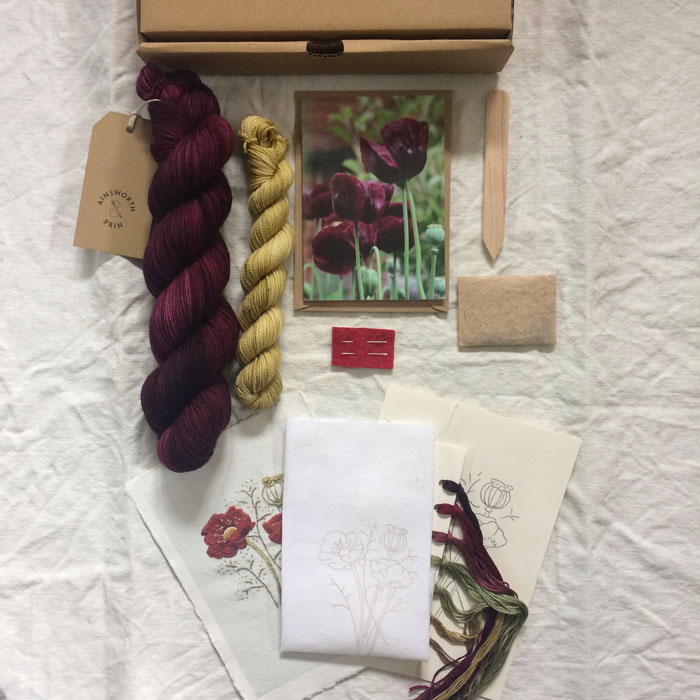 The contents of a club box laid out Dark plum yarn and a yellow mini skein, a greetings card, seed packet, handmade wooden label and an embroidery kit