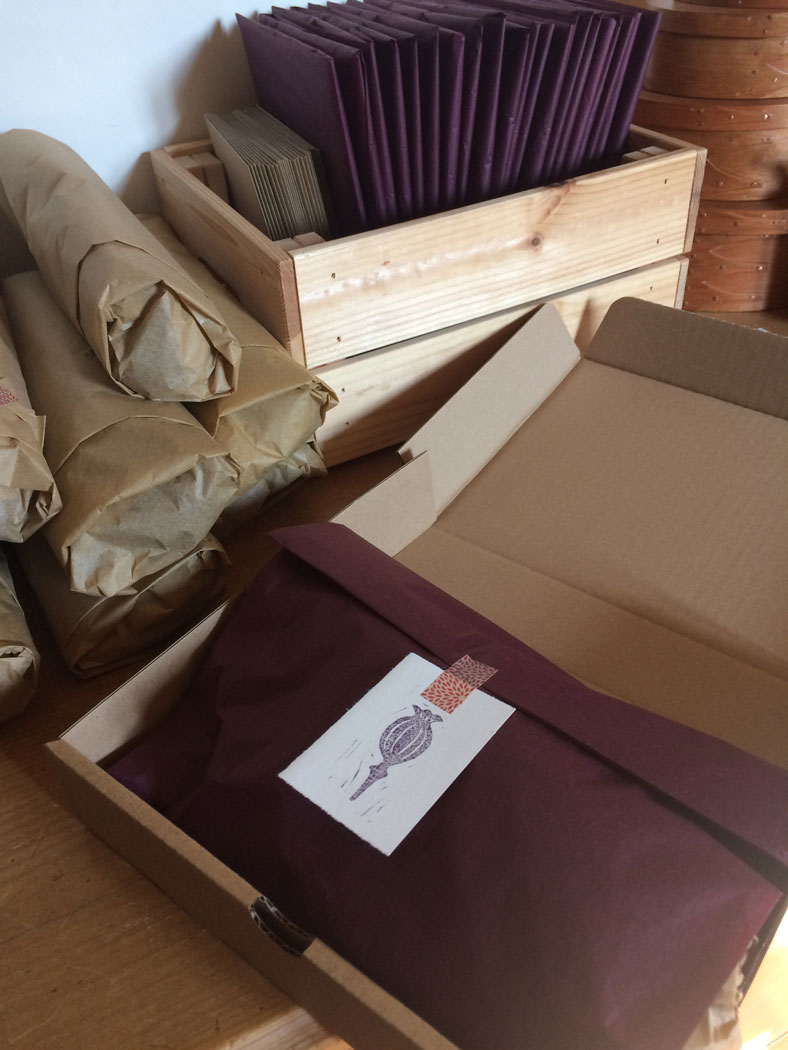 A packed up club box with wrapped yarn and packets behind it