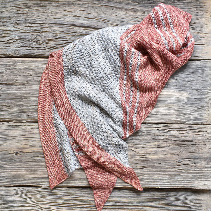 A knitted shawl with patterned panels in a speckled yarn broken up by bands of coral garter stitch