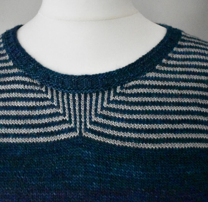 A close up of the neckline of a stripped knitted T-shirt showing a slip stitch pattern