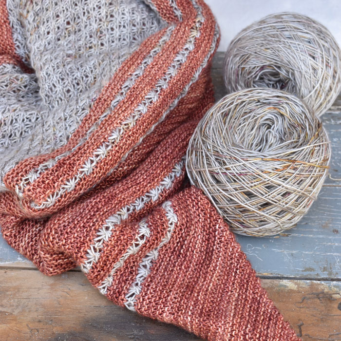 A close up of a knitted shawl with balls of the yarn used to make it