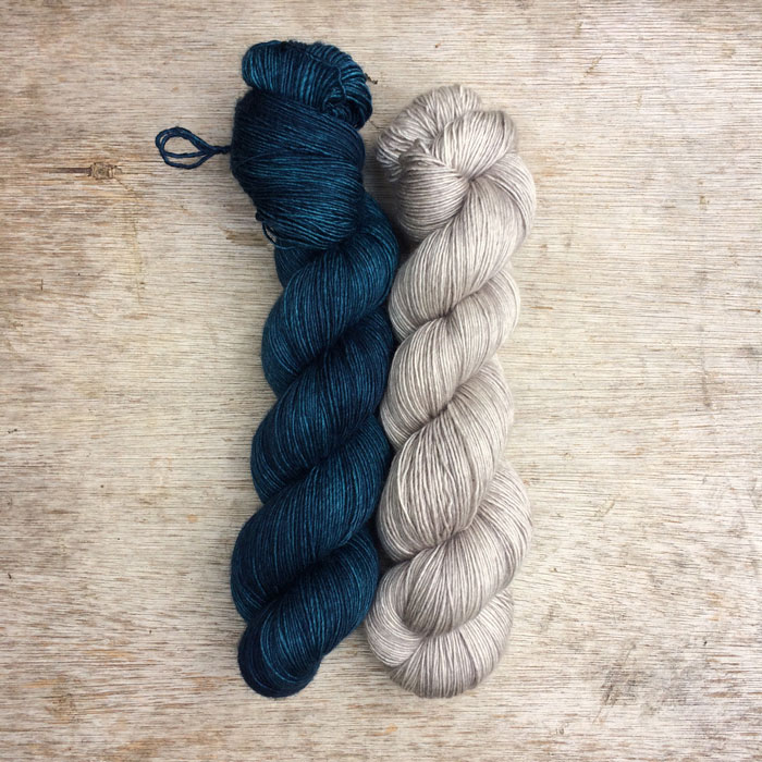 Two skeins of silky merino yarn one in a deep blue and the other a pale grey