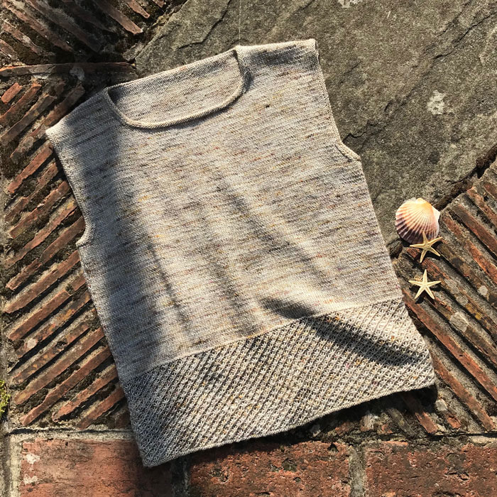 A knitted sleeveless top with a patterned band at the hem on a brick background