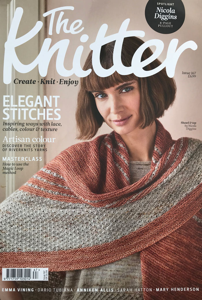 The cover of a knitting magazine with a model wearing a coordinating top and shawl in coral and speckled yarn