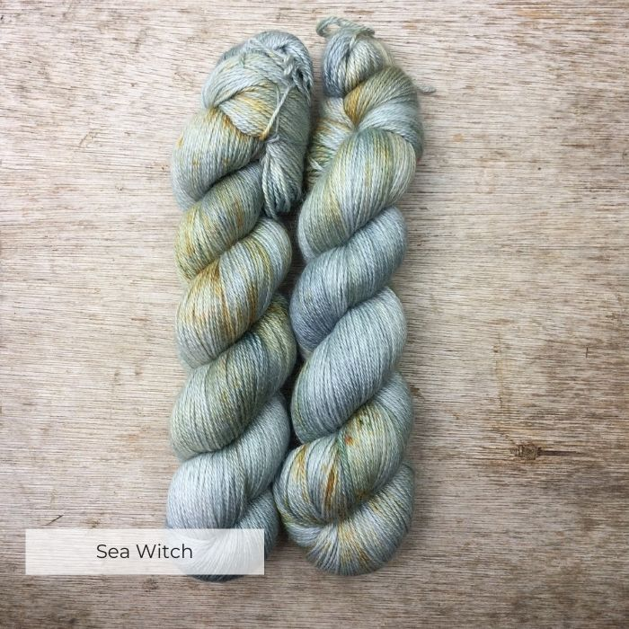 skeins of yarn dyed in shades of pale blue, green and grey with speckles of gold and deep green
