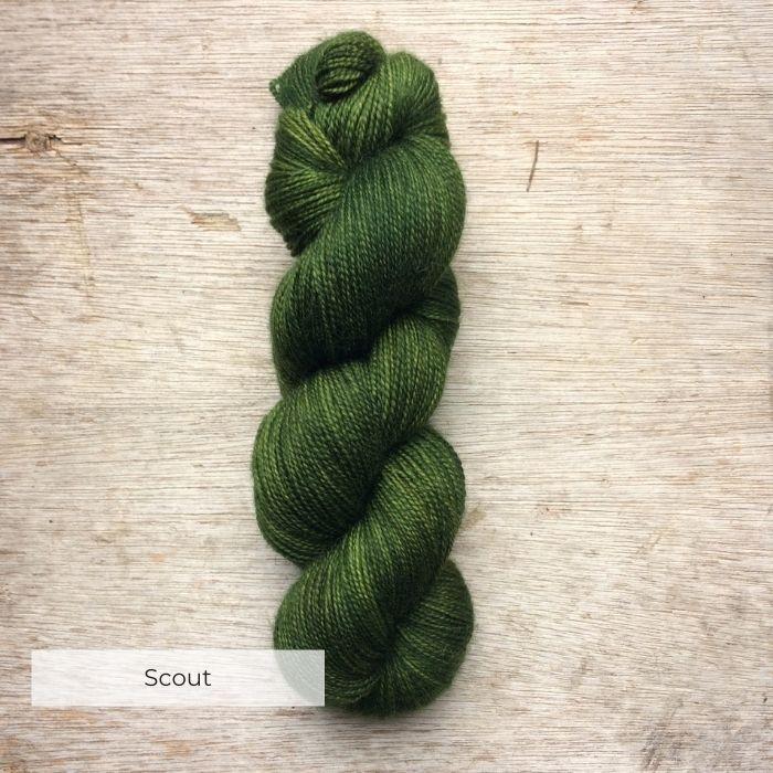 A single skein of leaf green sock yarn on a wooden background