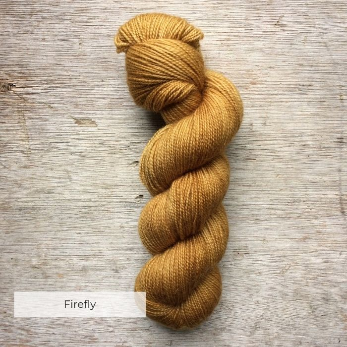 A single skein of soft golden yellow sock yarn on a wooden background