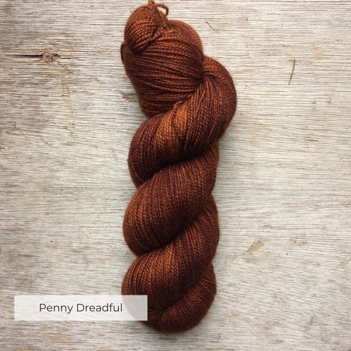 A single skein of deep rust sock yarn on a wooden background