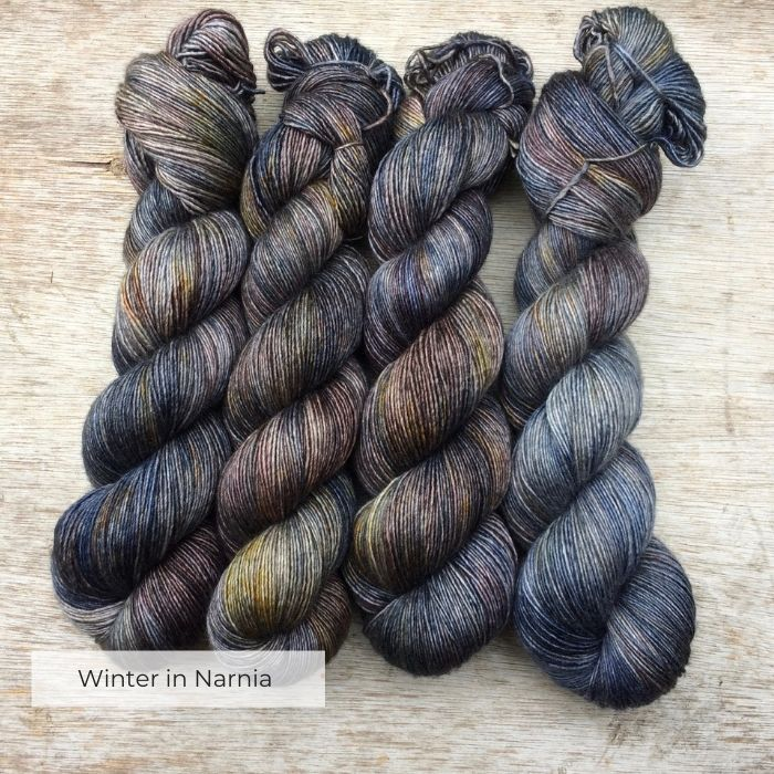 Four hanks of slightly silky yarn in shades of blue, brown, green, gold and plum