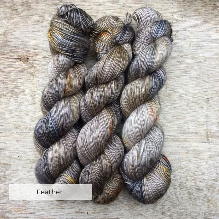 There hanks of silky yarn blue and gold splashes on a light brown base