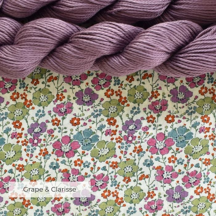 Two skeins of grape cotton yarn laying on a piece of flowery Tana Lawn fabric
