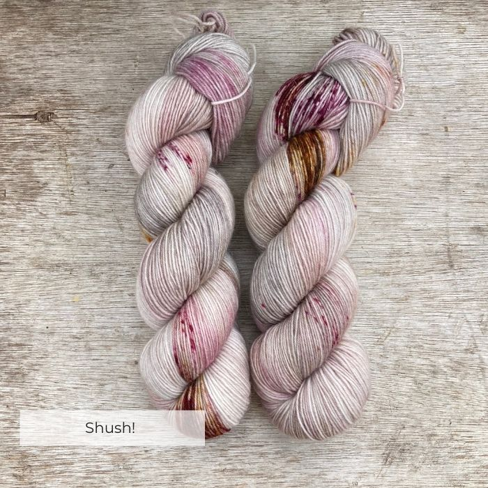 Two hanks of yarn dyed with splashes of rose pink, burgundy and bronze